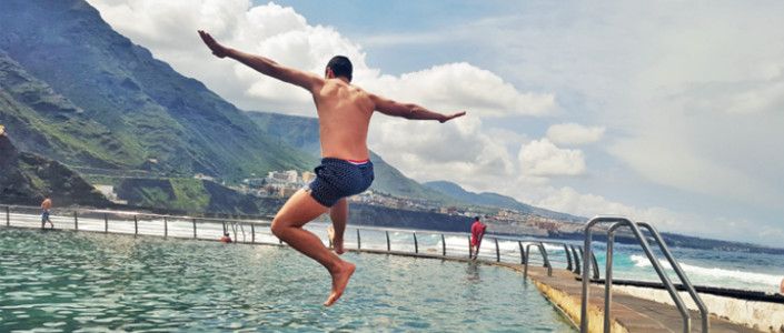 Jumping in a natural pool by the Atlantic